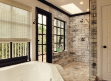 Black and white sophisticated bathroom with corner tub, double showers, marble wall tile, travertine floor tile, and woven natural shades