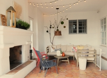 Spanish covered patio lounge with outdoor fireplace, string lights, sectional, and accent chairs