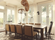 Contemporary dining room with elongated dining table and triple-pendant bentwood chandelier, high-back windsor end chairs, and cow print carpet tiles