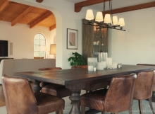 Classic, modern dining room in Spanish home with leather chairs and storage