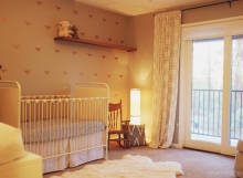 Neutral eclectic nursery - metal crib, rocking chair, and dragonfly wallpaper