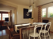 Eclectic dining room with white metal bistro chairs, 3-pendant glass chandelier and anchor wall art